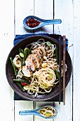 Chicken breast with spring onions and chilli peppers on a bed of noodles (Asia)