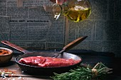 A raw beef steak being drizzled with olive oil