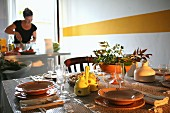 Gedeckter Tisch mit Weingläsern vor weisser Wand mit gelbem Streifen