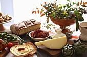 Apulisches Stillleben mit Käse, Brot, Gebäck und Gemüse