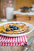 A stack of pancakes with icing sugar and blueberries