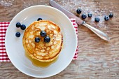 A stack of pancakes with sugar and blueberries (seen from above)