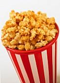 Caramel popcorn in a striped plastic bucket