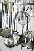 Various kitchen utensils hanging against a tiled wall in a kitchen