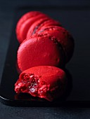 Classic raspberry macaroons, one with a bite taken out