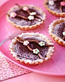 Chocolate tartlets decorated with sugar flowers and icing sugar