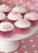 Decorated cupcakes in pink cases on white cake stand