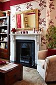 Wandgestaltung mit dunkelrotem Absatz über floraler Tapete in traditionellem Wohnraum; Antikspiegel über englischem Kamin