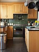 Einbauküche mit Eichenfronten im Landhausstil und dunkelgrünen Wandfliesen