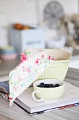 Cup of fresh blueberries and floral cloth in mixing bowl on recipe book