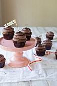 Chocolate cupcakes with chocolate cream and chocolate sprinkles on a pink cake stand