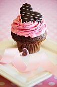 A rose cupcake decorated with a chocolate heart