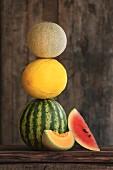 Verschiedene Melonen. gestapelt, auf rustikalem Holzbrett, ganz und aufgeschnitten