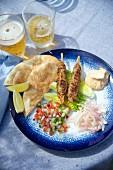 Lamb kebabs with pita bread, salad and harissa sauce