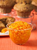 Carrot and pineapple jam in a glass bowl with muffins in the background