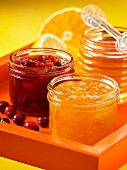 A jar of cranberry and orange marmalade and a jar of honey and lemon marmalade