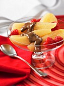 Poached pears with chocolate sauce and raspberries in a dessert bowl