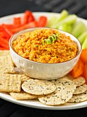 A vegetable platter with a fava bean dip and crackers