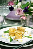 Tortellini with a pumpkin and mustard filling garnished with sage leaves and pine nuts