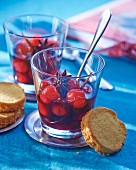 Cherry soup in glasses with star anise and biscuits