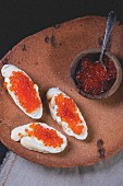 Slices of baguette topped with red caviar on an old terracotta platter