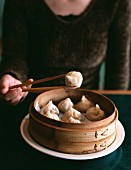 A woman with wooden chopsticks holding a steamed dumpling