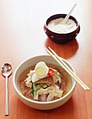 Korean beef soup with egg, radish, chilli, cucumber, pickled ginger, beef and wheat noodles made from red wheat