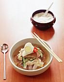 Koreanische Rindfleischsuppe mit Ei, Rettich, Chili, Gurke, eigelegtem Ingwer, Rindfleisch und Weizennudeln aus rotem Weizen