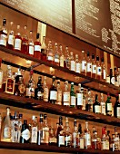 Bottles of spirits on a glass shelf behind a bar