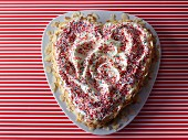A heart-shaped cake decorated with colourful sprinkles and flaked almonds