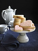 Heart-shaped cookies with pink icing on a cake stand