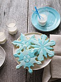 Snowflake cookies with blue icing and glasses of milk