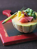 Fruit salad with kiwi, watermelon and grapes served in half a melon