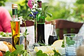 Vinegar, oil, wine, cheese and bread on a table laid outside