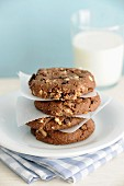 A stack of homemade hazelnut chocolate cookies with a glass of milk