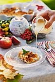 Ein Stück Apfel-Streusel-Kuchen wird mit Vanillesauce beträufelt