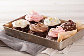 A tray of decorated cupcakes