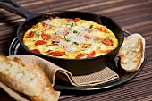 Tomato, fresh herbs and cheese frittata in a cast iron pan