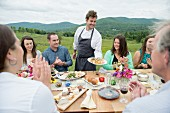 Family celebration outside; a young chef serving appetisers against a backdrop of green hills