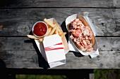 Lobster Roll (Baguettebrötchen mit Hummer) und Pommes frites mit Ketchup
