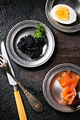 Black caviar, smoked salmon and a hard-boiled egg on three pewter plates