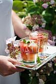 Frau trägt Tablett mit zwei Gläsern erfrischendem Früchte-Gurken-Drink