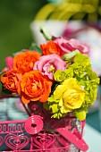 Bunter Blumenstrauß in einem Drahtkörbchen im Freien