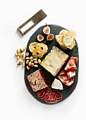 A charcuterie and cheese board with pistachios and fruits