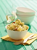 Potato salad with almonds in a wooden bowl for a picnic
