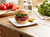 Hamburger with tomatoes, red onion and lettuce on a kitchen table