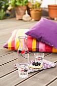 Tablett mit Erfrischungsgetränk, Gläsern und Törtchen auf Holzterrasse, im Hintergrund farbige Kissen