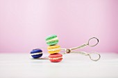 Colourful macaroons with a pair of silver tongs against a pink background