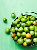 Green tomatoes in a metal bowl (seen from above)