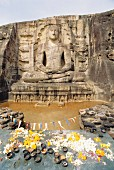 A seated Buddha carved into a mountain with offerings in front of it, Polonnaruwa, Sri Lanka